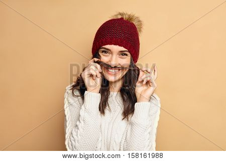 Young beautiful woman wearing winter outfit having fun in studio. Red hat and cozy white sweater. Hipster lifestyle. Cheerful girl making grimace faces