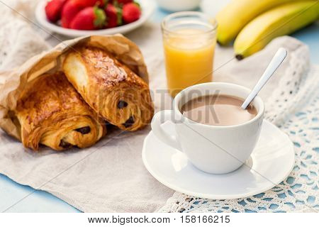 Cup of coffee with french croissant with chocolate served with fruit