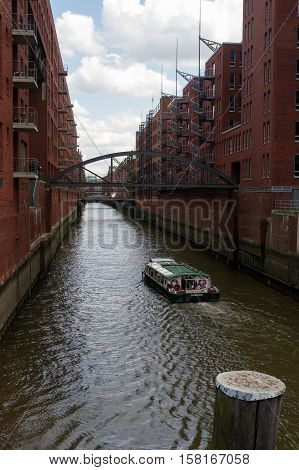 HAMBURG GERMANY - JULY 18 2015: a ferry on the canal of Historic Speicherstadt houses and bridges at evening with amaising skyview over warehouses famous place on Elbe river.