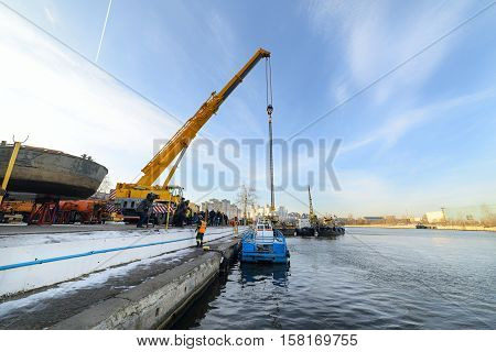MOSCOW, RUSSIA - NOVEMBER 11, 2016: State Unitary Enterprise Mosvodostok performs recovery vessels on coastal winter parking. Powerful truck crane vessel begins to rise out of the water.