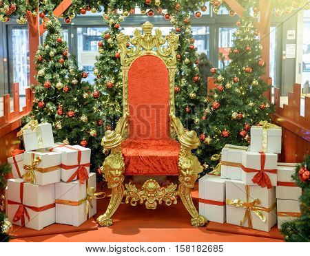 Luxurious red chair Santa Claus throne surrounded by multiple gift boxes