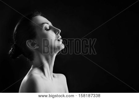 sensual aroused woman profile on black background with copyspace monochrome