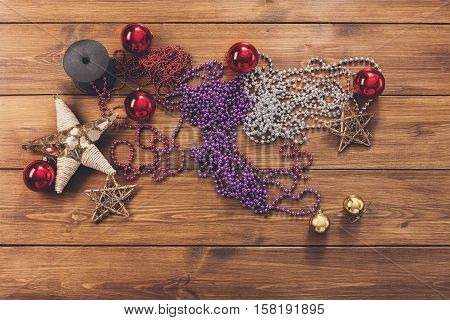 Prepare for christmas eve or other winter holidays. Xmas tree decorations, and bead garlands concept background, top view on wood. Ornaments, tinsel, stars, spruce branch and balls