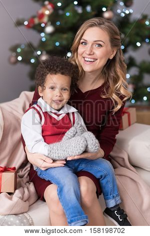 Happy motherhood. Good looking charming blonde woman sitting on the sofa and having her son on her lap while celebrating Christmas