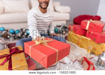 Gift for you. Selective focus of a Christmas present being wrapped in a wrapping paper and being offered to you while being held by a positive cute young man