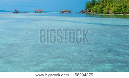 Bay with Underwater Corals in Front of Diving Station and Guesthouses on Kri Island, Raja Ampat, Indonesia, West Papua.