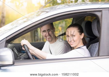 Lifestyle portrait of young confident happy woman driving, smiling casual man sitting near in the car, family travelling by car, woman taking driving courses