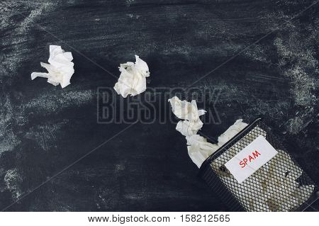 crumpled paper sheets full trash spam sign on dirty black background