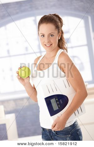 Pretty girl holding scale and apple in hands, smiling, dieting.?