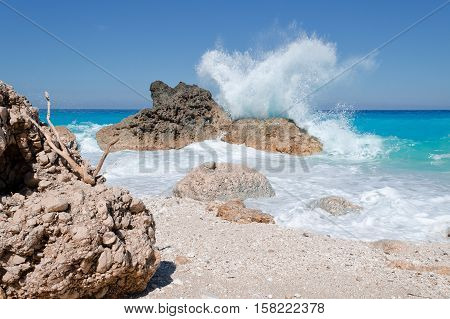 Big wave crashing over a boulder on the beach Kavalikefta on Ioian island Lefkada