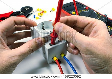 Measurement of voltage in electrical outlet with a multimeter on a white background