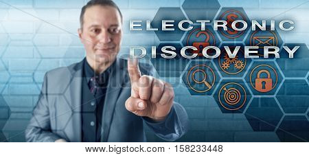 Smiling male governmental investigator pushing ELECTRONIC DISCOVERY on an interactive touch screen. Information technology concept touching on litigation digital evidence email and civil procedure.