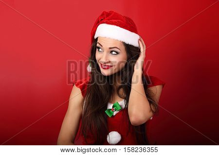 Beautiful Thinking Grimacing Woman In Santa Claus Christmas Costume Scratching The Head On Red Backg