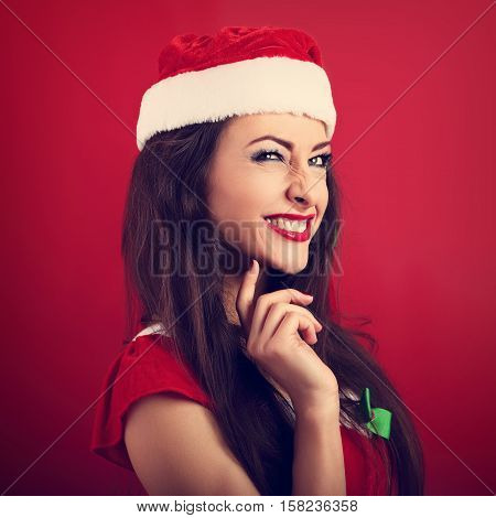 Fun Squint Excited Grimacing Woman In Santa Claus Christmas Costume Looking Up On Bright Red Backgro
