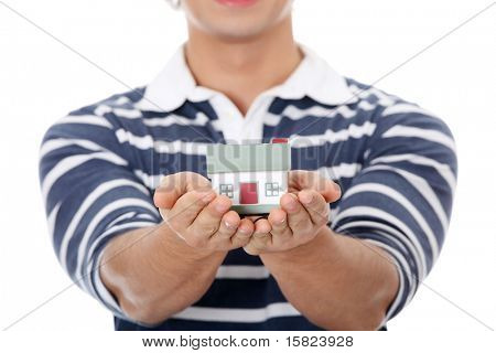 Young man with house's model. Isolated on white background.