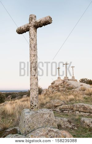 Three Crosses of carved stone on granite rock at dusk of Heaven