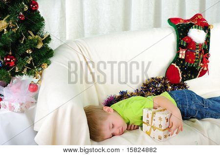 the little boy fell a sleep on the couch waiting for a holiday. Happy New Year and Merry Christmas!