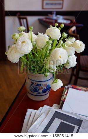 Ranunculus bouquet in a vase in a cafe room in Heidelberg in Baden-Wurttemberg in Germany.