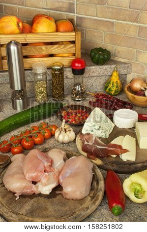 Raw chicken breast fillets on kitchen breadboard. Preparation of home diet meals with vegetables and cheese. Dietary chicken meat.
