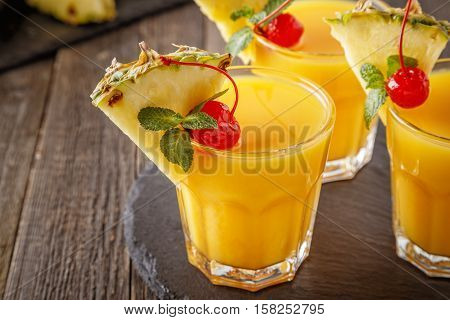 Glasses of pineapple juice with pieces of pineapple cocktail cherry and mint on wooden table healthy drink concept.