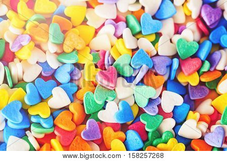 Heap of colorful candies confetti of heart shape abstract background Valentine Day holiday concept macro photograph horizontal