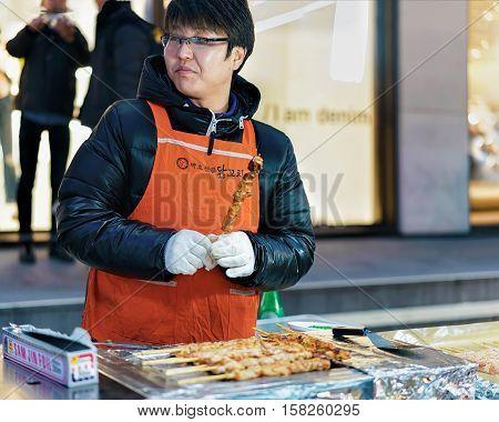 Woman Seller Of Kebab Skewers In Myeongdong Street Market Seoul