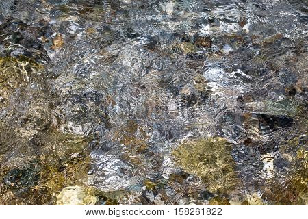 Close up of river stream water surface background texture during high water flow at springtime