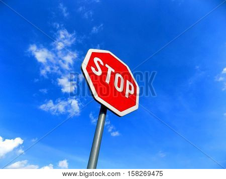 Stop roadsign and blue sky during sunny day
