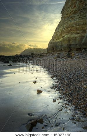 Beautiful Sunrise Landscape Over Sandy Beach With Rock And Cliff Detail On England's South Coast