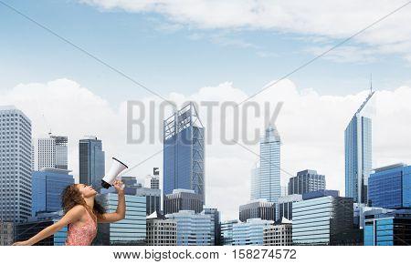 Young woman against city background screaming emotional in megaphone