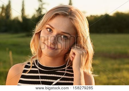 A nice-looking girl with magic smile looking straightly in the camera and listening to the music with her earphones. A girl touching her earphones with her hand.