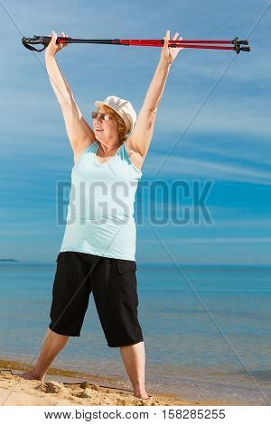 Senior woman enjoying nordic walking doing warmup exercises with poles on sea shore sunny summer day. Health activity in old age.