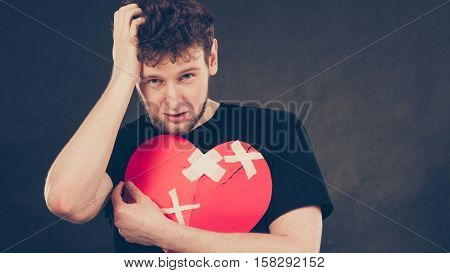 Separation and conflict. Young upset sad man with red heart glued by plaster. Guy lost his love relationship. Valentines Day.