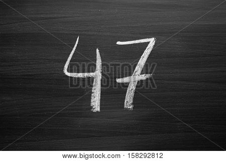 number forty seven enumeration written with a chalk on the blackboard