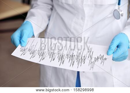 Cardiologist with stethoscope holding cardiogram in hospital