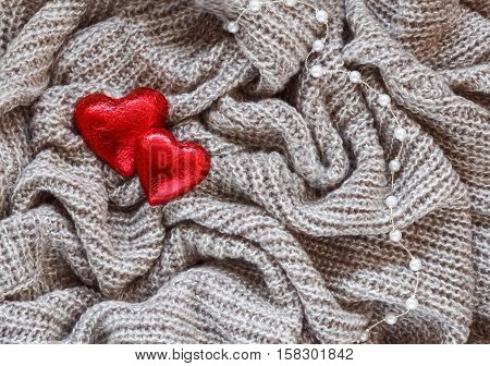 Closeup macro texture of knitted wool fabric material with red candy heart and white pearl bead necklace on top clothing background with wrinkles and folds Valentine holiday card love concept