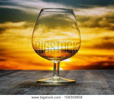 Glass of brandy on evening sky background.