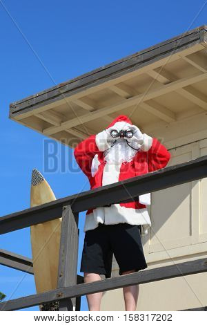 Santa Claus Life Guard. Santa Lifeguard. Santa Claus is a lifeguard at the beach in a lifeguard tower outside.
