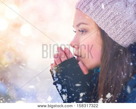 Winter girl blowing on her hands, cold weather. Snow. Frost, Freeze, Teenage Model Girl walking in winter park. Beautiful young woman outdoors. Cold weather concept, frozen hands