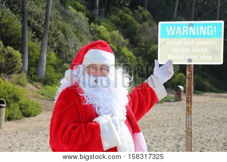 Santa Claus points to a Warning Sign at the beach. Santa Warning. Santa Claus Danger. Santa Claus beach.