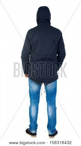 Back view of handsome man in winter jacket  looking up.   Standing young guy in parka. Rear view people collection.  Man in warm jacket hood pulled on his head standing and looking.