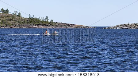 HIGH COAST HERITAGE, SWEDEN ON SEPTEMBER 05. View of the small boat at sea on September 05, 2016 in Barsta, Sweden. Unidentified men on board. Sunshine and islands. Editorial use.