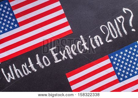 What to Expect in 2017 on the chalk board and US flag. Election concept
