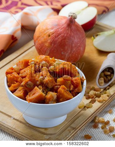 Pumpkin dessert with apple, cinnamon and raisins in white bowl on the wooden board.
