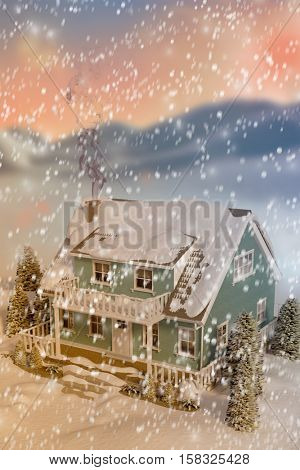 3D High angle view of house covered in snow against digitally generated snowy land scape