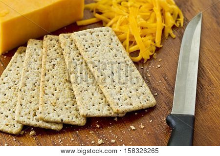Yellow grated and whole cheddar cheese and crackers on a wooden cutting board background