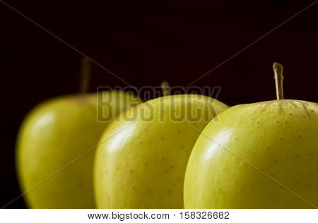 three fresh tasty apples closeup on a dark background in early morning light
