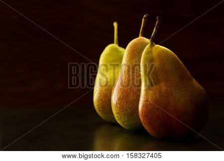 three tasty sweet pears in a row on a dark background in morning light