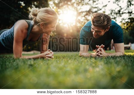 Fit Young Man And Woman Exercising In Park