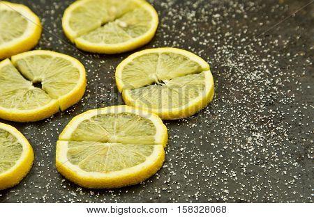 Slices of sour lemons with sprinkled sugar on a dark grey background